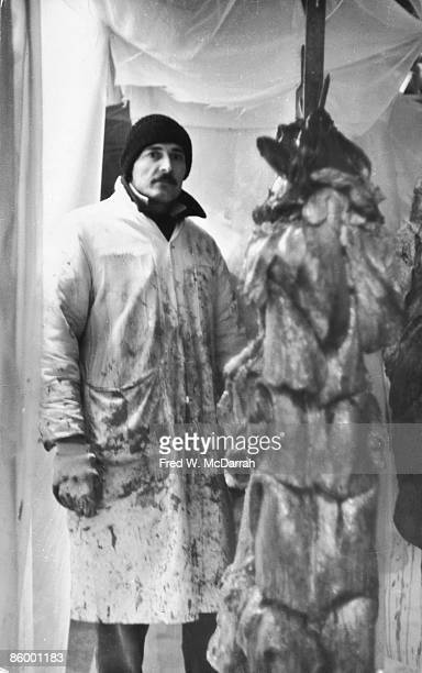 American performance artist Robert Delford Brown poses in a knit cap gloves and a long bloodspattered coat during the performance of his 'Meat Show'...