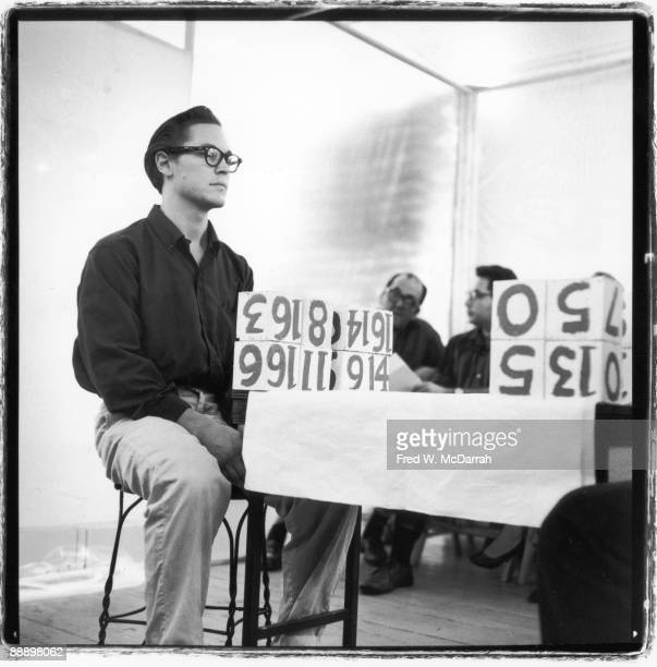 American performance artist Robert Whitman plays a game involving large numbered blocks during Allan Kaprow's '18 Happenings in 4 Parts' at the Ruben...