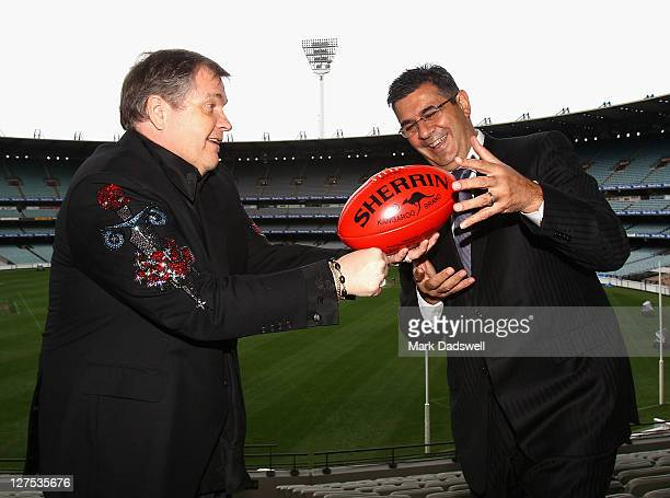 American performer Meat Loaf handballs to AFL Chief Executive Officer Andrew Demetriou during an AFL Grand Final entertainment press conference at...