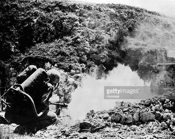 American Pfc. Joseph Garrity fires a blast from a flame thrower at a Japanese soldier who refused to abandon the tomb he was using as a sniper's nest.