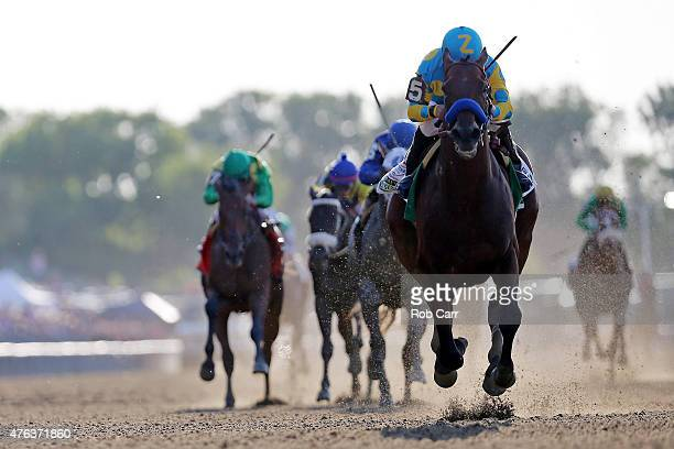American Pharoah ridden by Victor Espinoza crosses the finish line ahead of Frosted ridden by Joel Rosario and Keen Ice ridden by Kent Desormeaux to...