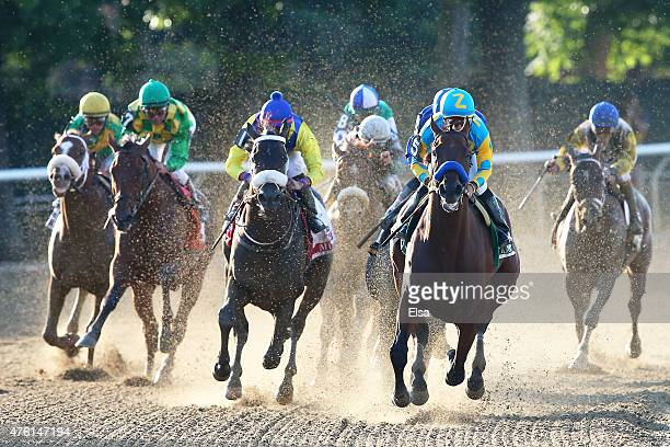 American Pharoah ridden by Victor Espinoza leads the field out of the fourth turn during the 147th running of the Belmont Stakes at Belmont Park on...