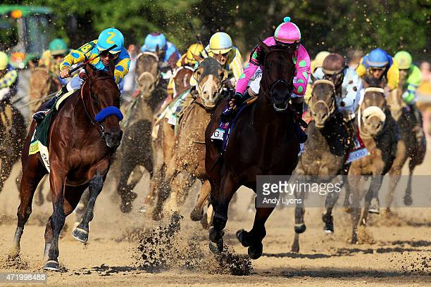 American Pharoah ridden by Victor Espinoza races Firing Line ridden by Gary Stevens out of turn 4 during the 141st running of the Kentucky Derby at...