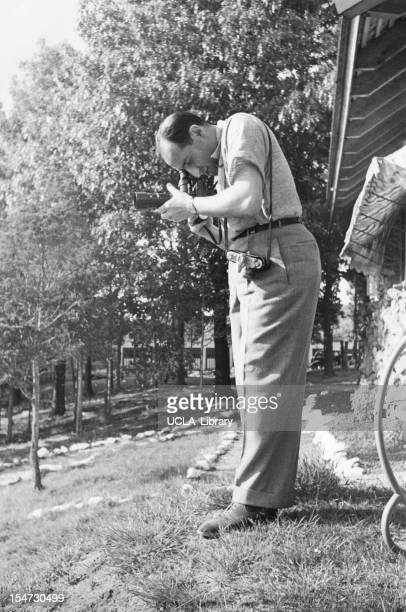 American photographer Alfred Eisenstaedt looks through a viewfinder as he lines up a shot, mid 20th century.