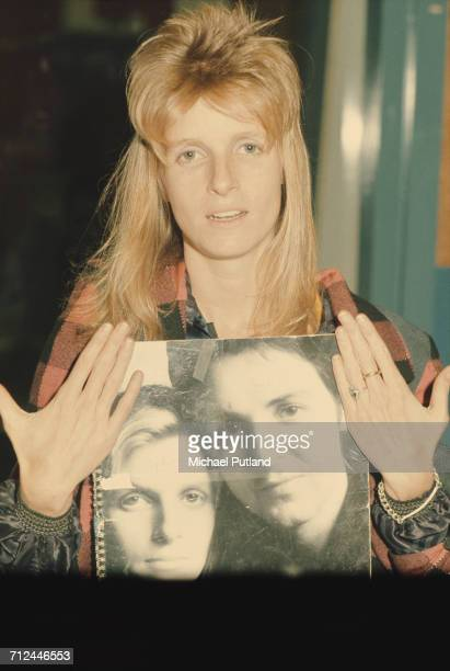 American photographer and musician with rock group Wings Linda McCartney pictured holding a spiral bound book with a cover image featuring a portrait...