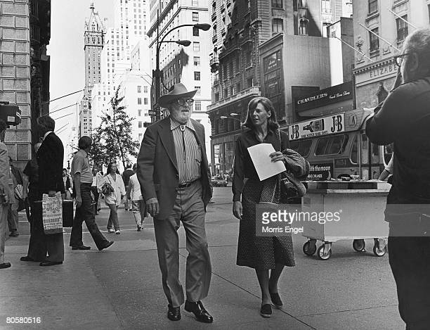 American photographer Ansel Adams walks along 5th Avenue with an unidentified woman New York New York late 1970s