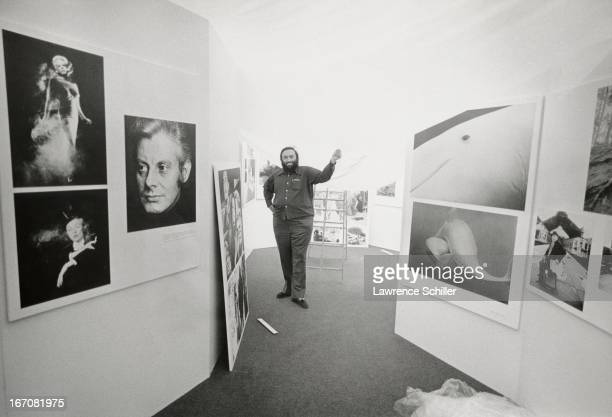 American photographer Lawrence Schiller poses among photographs by British photographer Antony ArmstrongJones 1st Earl of Snowdon during an...