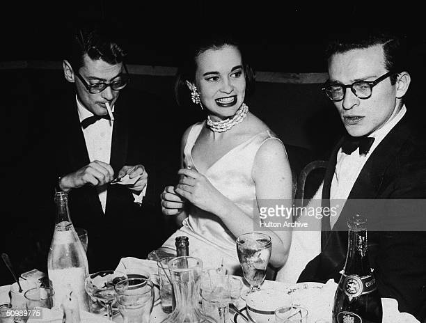 American photographer Richard Avedon , American heiress and designer Gloria Vanderbilt, and American film director Sidney Lumet, sit at a table...