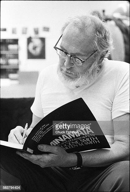 American photographer W Eugene Smith autographs a copy of his book 'Minamata' as he sits in his loft New York New York January 1976
