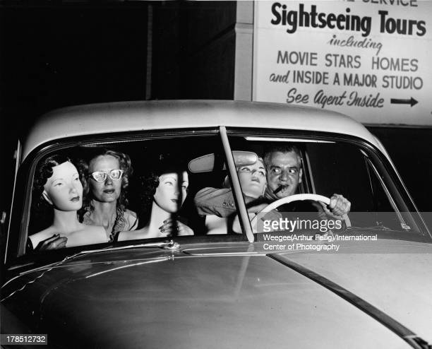 American photographer Weegee and an unidentified woman sit in the front seat of a car with a trio of mannequins ca 1950 Photo by Weegee/International...