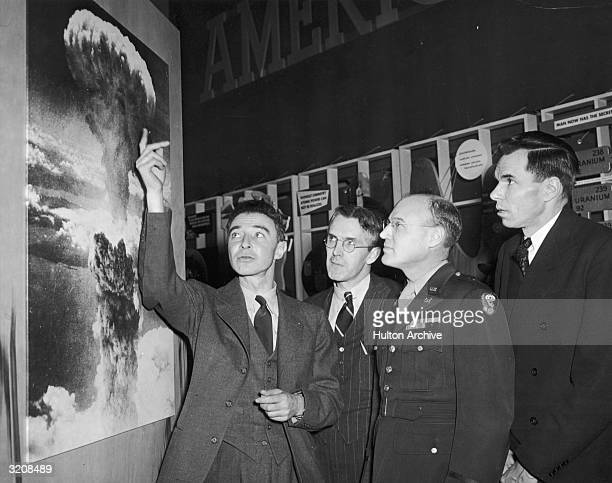 American physicist Dr. Robert Oppenheimer , points to a picture of the atomic bomb explosion over Nagasaki, Japan, as scientist Henry D. Smyth ,...