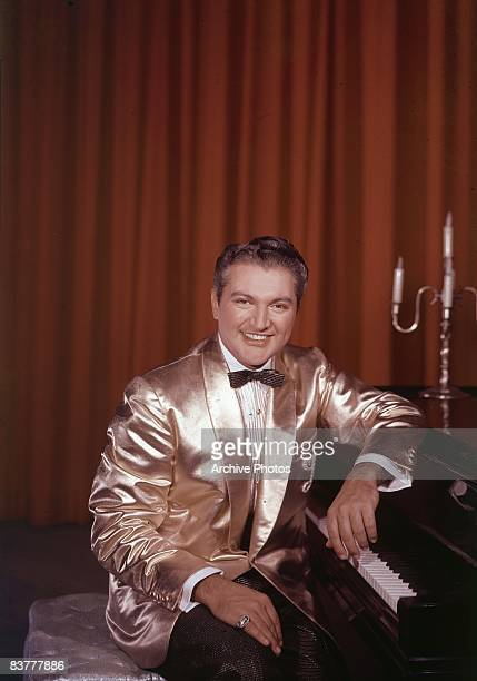 American pianist and entertainer Liberace sitting at a piano wearing a gold lame suit 1950s