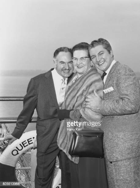 American pianist and singer Liberace born Wladziu Valentino Liberace with his brother George and mother Frances on the deck of the 'Queen Mary'...