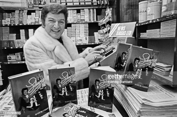 American pianist and singer Liberace with copies of his autobiography at a news kiosk, UK, 29th November 1973.