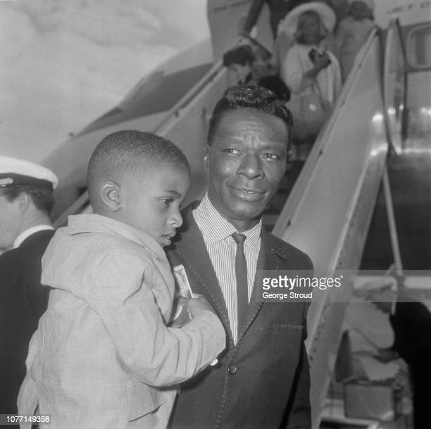 American pianist and singer Nat King Cole pictured with his son Nat Kelly Cole as they arrive at London Airport on 11th July 1963