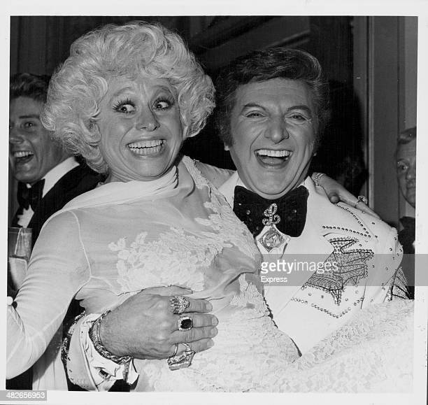 American pianist Liberace posing with British actress Barbara Windsor in his arms at the London Palladium England April 27th 1978
