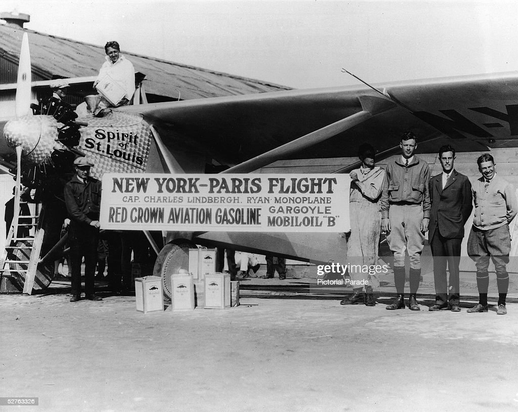 American pilot Charles A. Lindbergh (1902 - 1974) (third right) and others pose Lindbergh's recently purchased plane, the Spirit of St. Louis, San Diego, early 1927. Shortly after the picture was taken Lindbergh broke the speed record for trans-continental US flights. Also pictured are H. J. van der Lende (pouring fuel into the plane), welding foreman O. R. McNeel (at left, holding sign), student mechanic George Hammond (fourth right), Lindbergh, chief engineer Donald Hall, and A. J. Edwards. The banner advertises Lindbergh's forthcoming trans-Atlantic flight, completed on May 21.