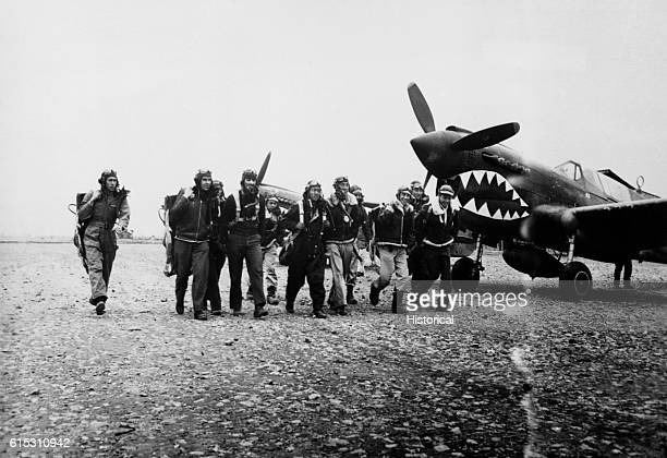American pilots wearing parachute packs walk in front of their Flying Tigers fighter planes. The Flying Tigers flew in China with the Nationalist...