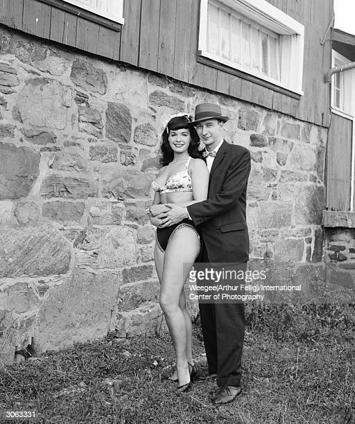 American pinup Bettie Page Playboy playmate of the month for January 1955 in the arms of a young man 1950s Photo by Weegee/International Center of...