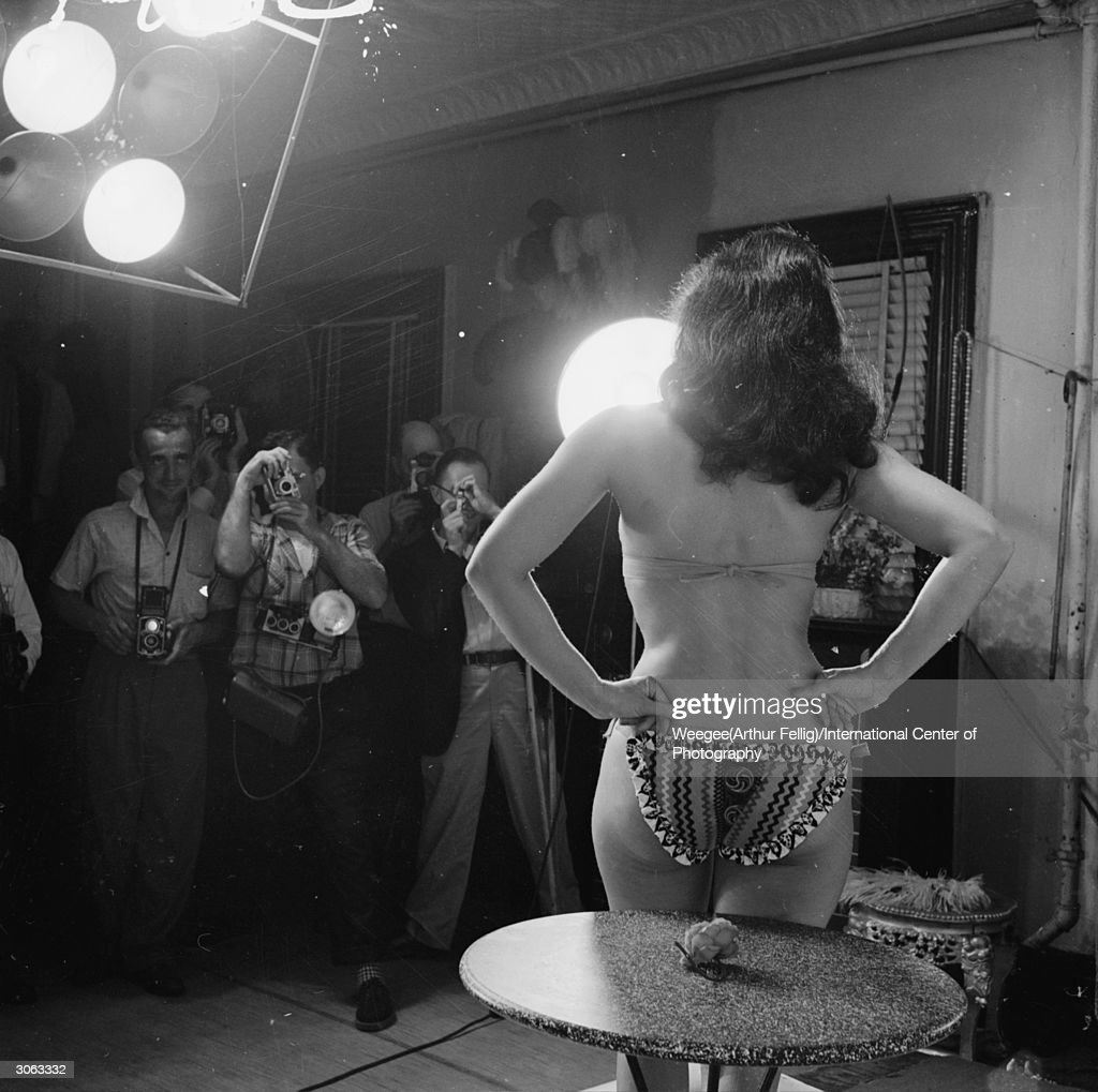 American pin-up Bettie Page, Playboy playmate of the month for January 1955 poses for a group of eager photographers, 1950s. (Photo by Weegee(Arthur Fellig)/International Center of Photography/Getty Images)