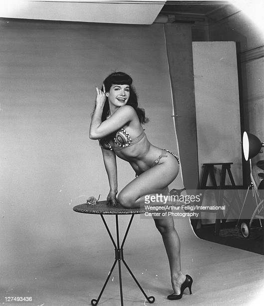 American pinup model Bettie Page 2008 in heels and a bikini poses on a circular table in a photo studio in front of flat studio background paper mid...