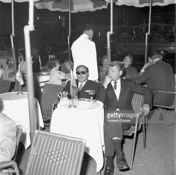 American playwright Tennessee Williams in a cafe with his friend in Via Veneto, Rome in 1958.