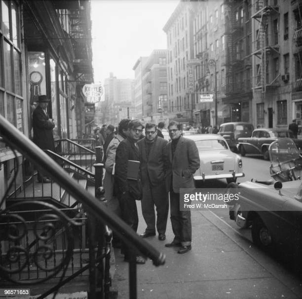 American poet Allen Ginsberg as he stands with his longtime companion Peter Orlovsky and several unidentified others near the Kettle of Fish bar New...