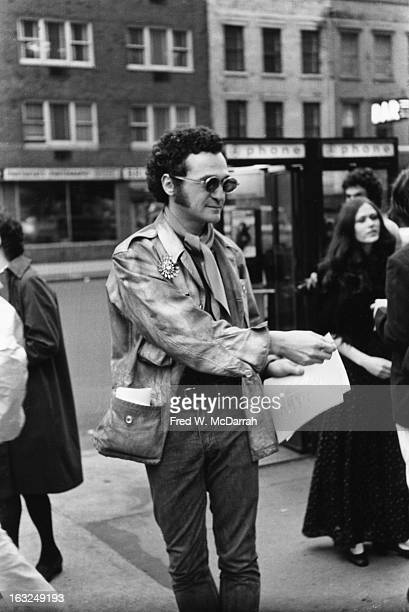 American poet and performance artist John Giorno passes out poems to passersby on Fifth Avenue New York New York April 18 1969