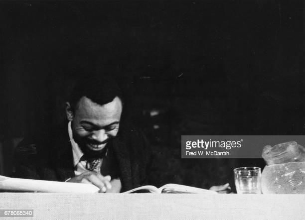 American poet and playwright LeRoi Jones laughs as he sits at a table during a benefit for Yugen Press at the Living Theatre New York New York...