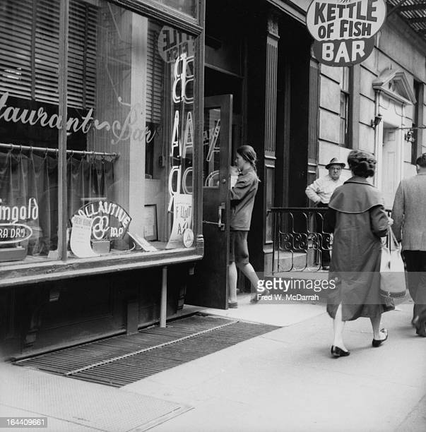 American poet Brigid Murnaghan carries her infant daughter Annie into the Kettle of Fish bar New York New York May 10 1959
