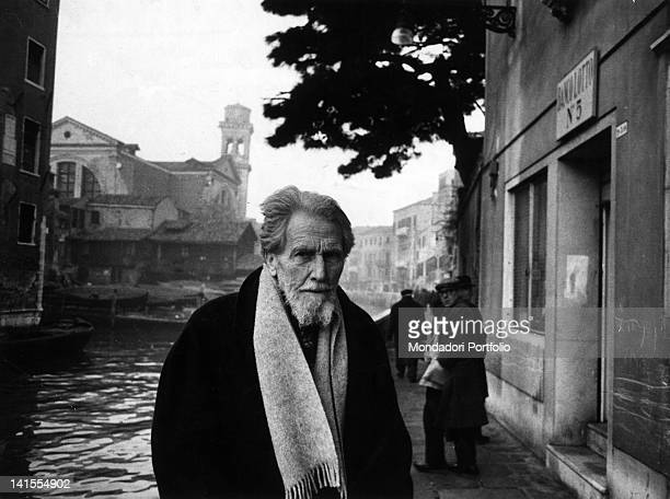 American poet Ezra Pound standing on a pavement nearby a canal Venice 1963