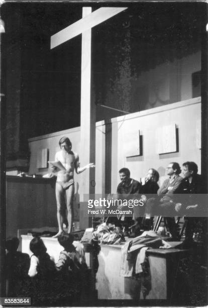 American poet Peter Orlovsky dressed in underwear and eyglasses reads from his collection 'Clean Asshole Poems' under a giant wooden cross at Judson...