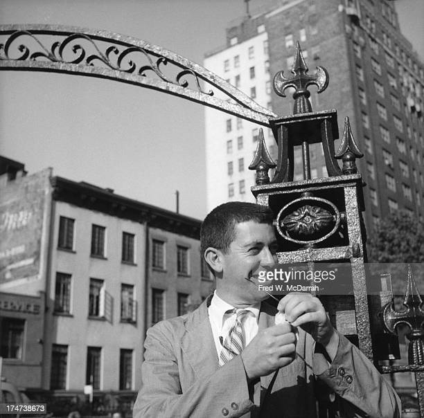 American poet playwright and academic Kenneth Koch smiles as he cleans his glasses in Sheridan Square Park New York New York September 29 1959