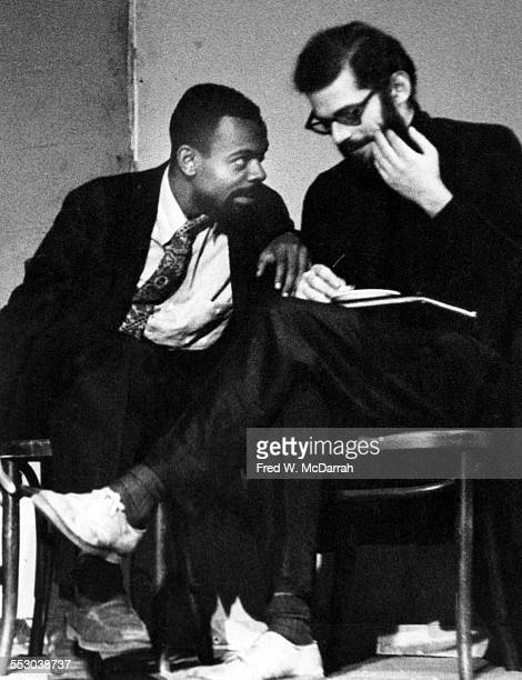 American poets LeRoi Jones and Allen Ginsberg converse on stage during poetry reading at the Living Theatre New York New York November 2 1959