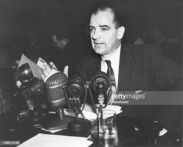 American politian US Senator Joseph R. McCarthy speaks from behind a bank of microphones, mid 20th century.