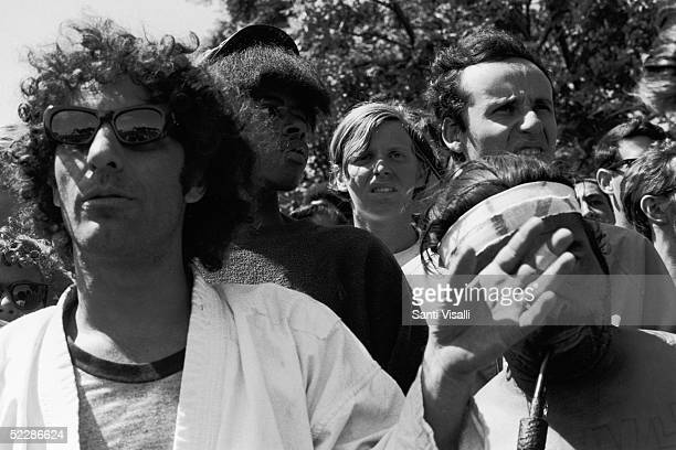 American political activist Abbott Abbie Hoffman gestures as he stands in the midst of a crowd of demonstators gathered in protest of the Democratic...
