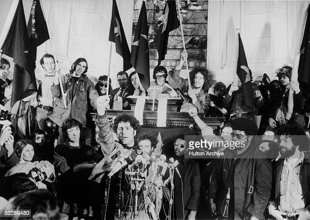 American political activist Abbott 'Abbie' Hoffman raises a fist from behind a bank of microphones during an unidentified rally in New York late 1960s