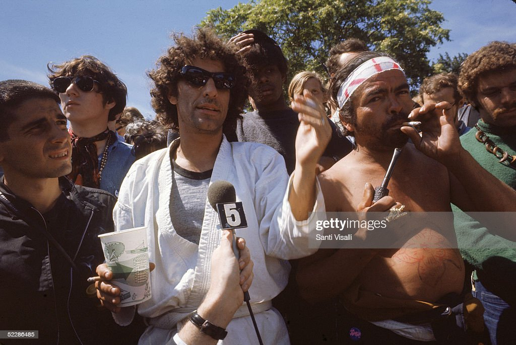 American political activist Abbott 'Abbie' Hoffman (1936 - 1989) speaks to a journalist from the midst of a crowd of demonstators gathered in protest of the Democratic National Convention in Grant Park, Chicago, Illinois, August 28, 1968.