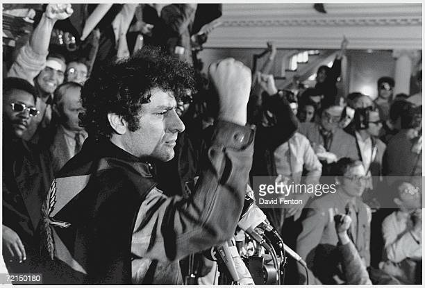 American political activist and founder of the Yippies Abbie Hoffman wears a party flag around his neck like a cape as he raises his fist in...