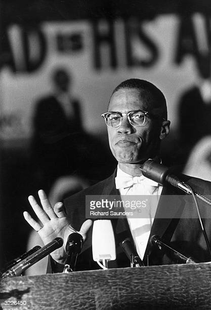 American political activist and radical civil rights leader, Malcolm X standing at a podium during a rally of African-American Muslims held in a...