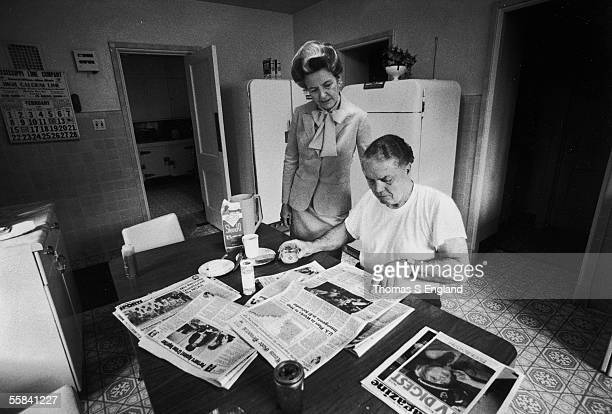 American political activist Phyllis Schlafly dressed in a suit with a large bow stands and reads the front page of the St Louis GlobeDemocrat over...