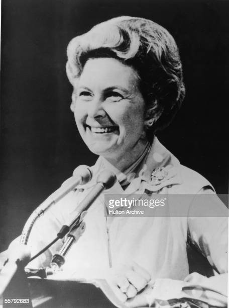 American political activist Phyllis Schlafly smiles from behind a pair of podium mounted microphones 1982