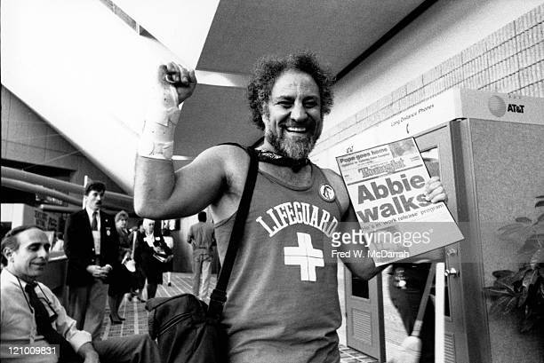 American political and social activist Abbie Hoffman laughs as he walks along a concourse of the Omni Coliseum at the Democratic National Convention...