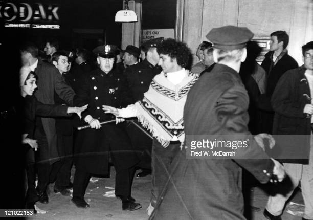 American political and social activist Anita Kushner reaches towards her husband Abbie Hoffman as police officers break up a sitdown demonstration...