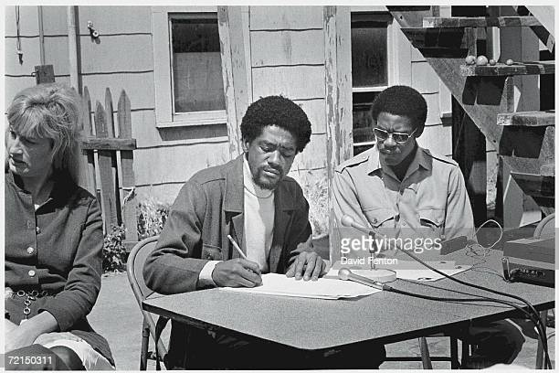 American political and social activists and Black Panther Party members Bobby Seale and David Hilliard sit at a table in front of the Party...