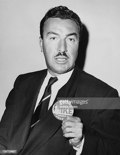 American politician Adam Clayton Powell Jr wears a badge supporting US Presidential candidate Dwight D Eisenhower in the press room at the Federal...
