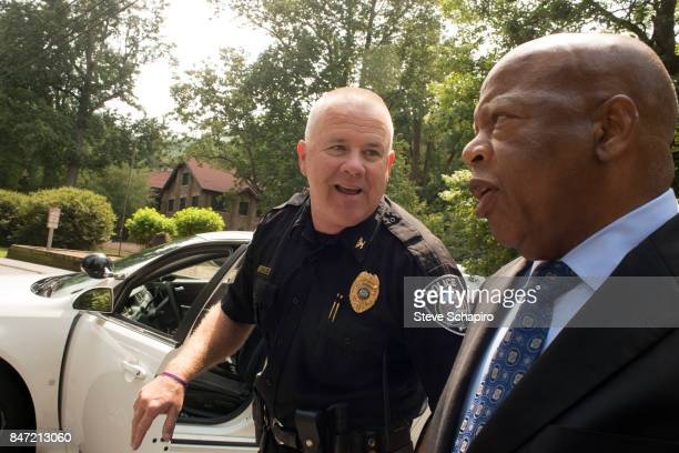 American politician and Civil Rights activist US Representative John Lewis speaks with a police officer outside the Montreat Conference Center during...