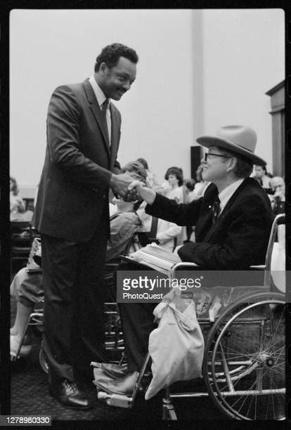 American politician and Civil Rights & religious leader Reverend Jesse Jackson shakes hands with disability advocate Justin Dart Jr during a House...