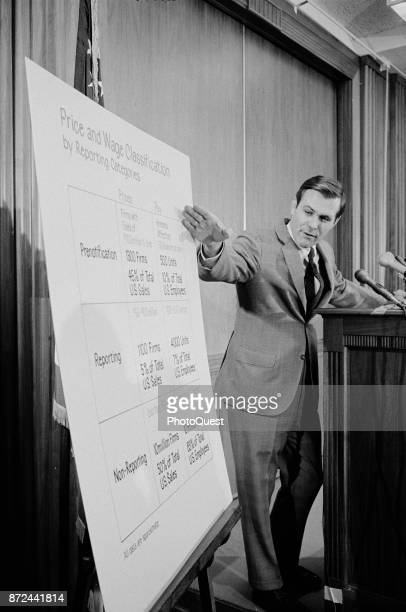American politician and Director of the Cost of Living Council Donald Rumsfeld gestures towards a chart headed 'Price and Wage Classification by...