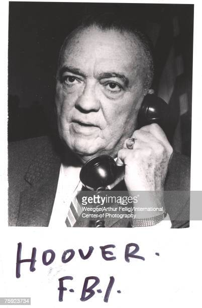 American politician and FBI Director J Edgar Hoover holds a telephone to his ear 1950s The text reads 'Hoover FBI' Photo by Weegee/International...
